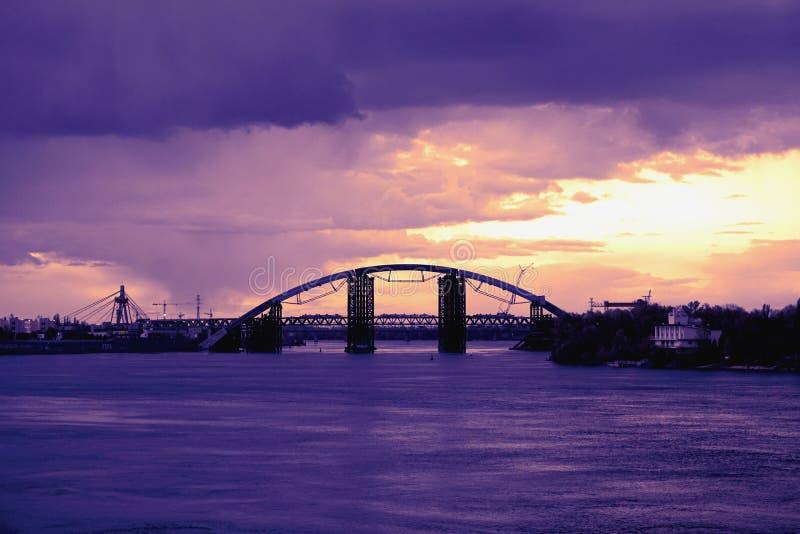 Tienda un puente sobre la reflexión en la superficie del agua del tiempo duaring de la puesta del sol de Dnieper del río foto de archivo libre de regalías