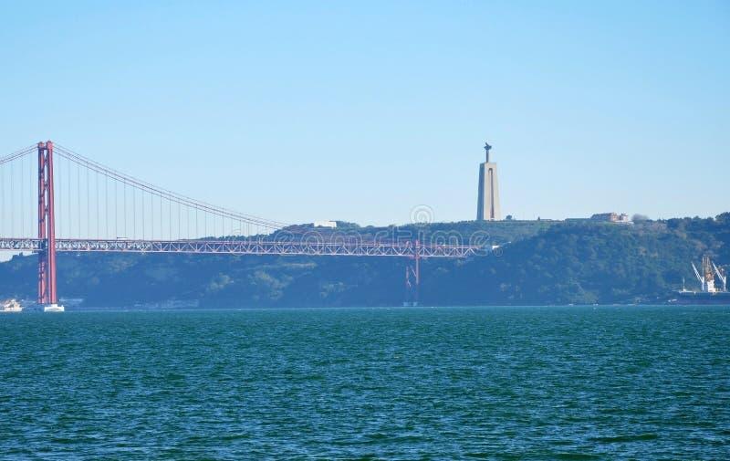 Tienda un puente sobre a Vasco da Gama, Portugal, estatua de Jesus Christ en Almada fotografía de archivo libre de regalías