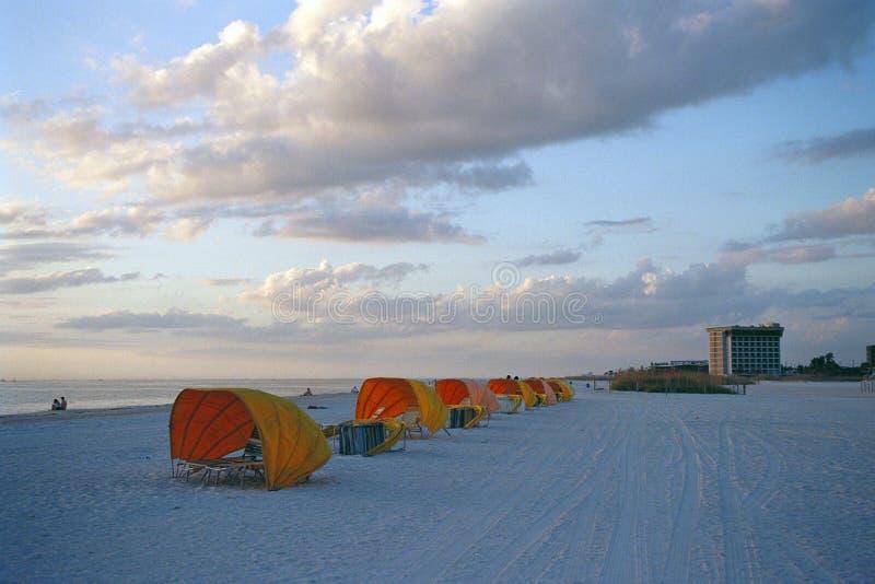 Tiendas amarillas de la playa en la puesta del sol foto de archivo libre de regalías