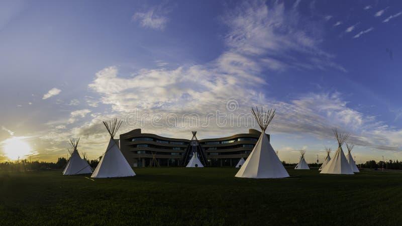 Tiendas de los indios norteamericanos del nativo americano en las praderas en la puesta del sol foto de archivo