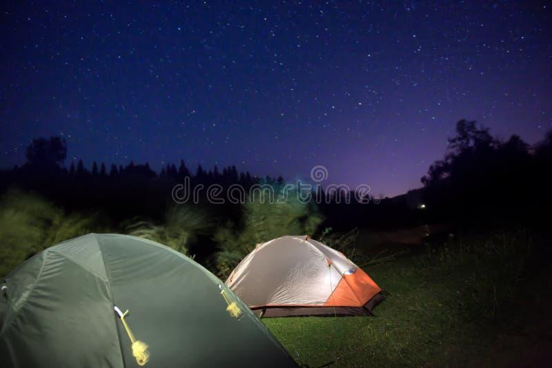 Tiendas en montañas debajo del cielo nocturno fotografía de archivo