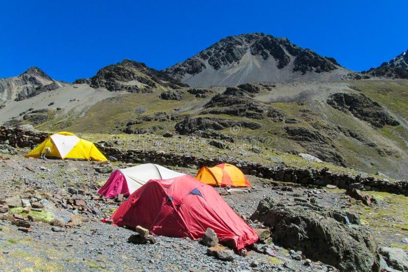 Tiendas rojas y amarillas en las rocas en las montañas fotos de archivo