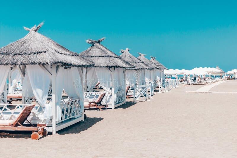 Tiendas y paraguas blancos en la orilla arenosa con el cielo azul de la belleza mágica imágenes de archivo libres de regalías