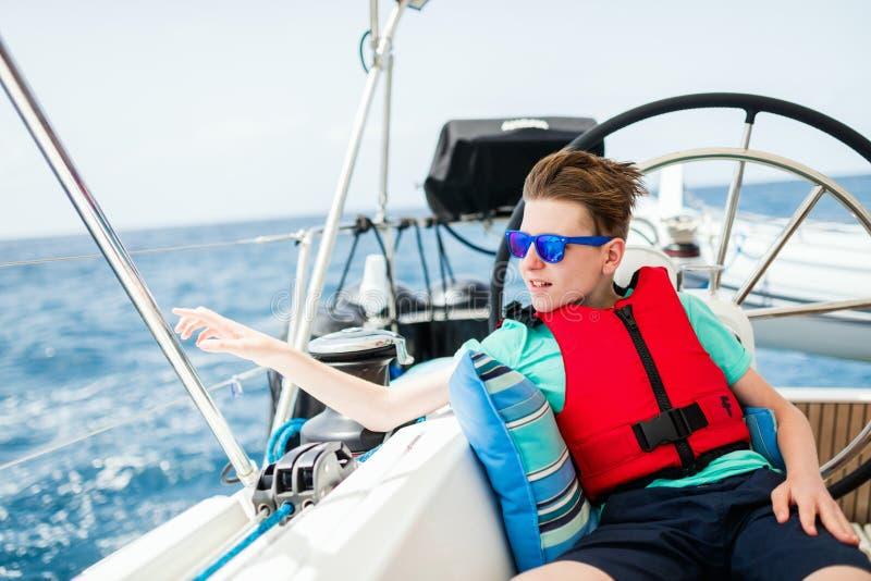 Tiener aan boord van varend jacht stock afbeeldingen