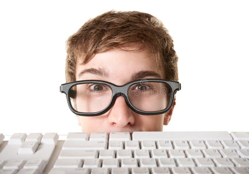 Tiener achter het Toetsenbord van de Computer stock afbeeldingen