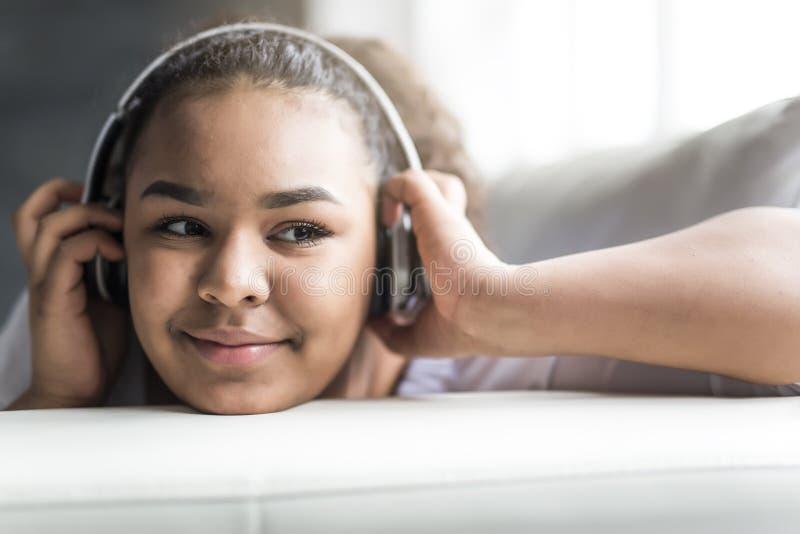 Tiener Afrikaanse jonge vrouw die thuis ontspannen royalty-vrije stock afbeelding