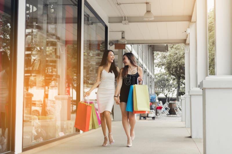 Tiener Aziatische vrouwen die en samen het winkelen lopen doen stock foto's