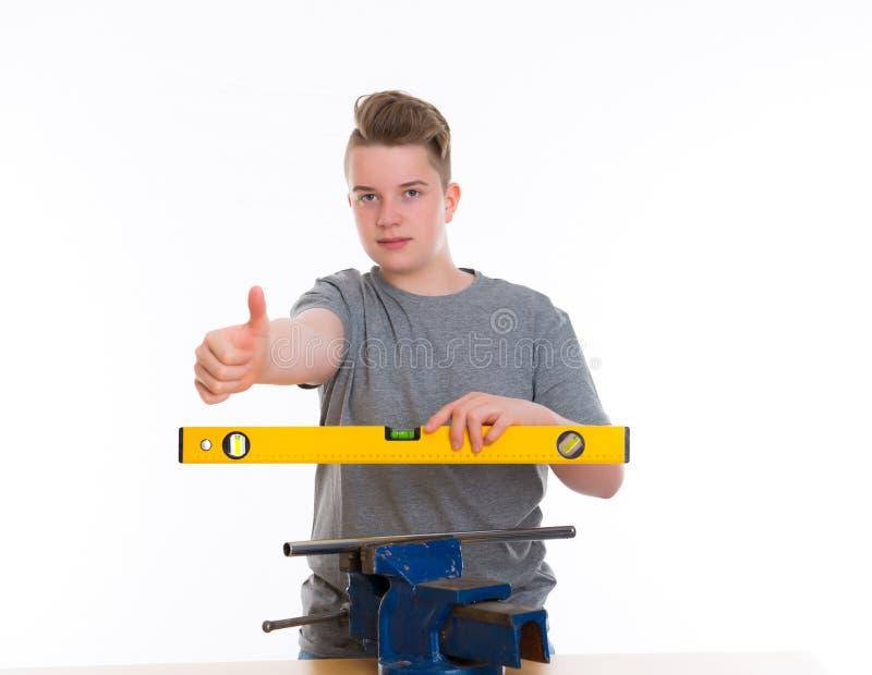 Tiener in beroepsopleiding met omhoog waterpas en duim royalty-vrije stock foto's