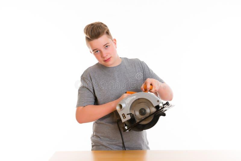 Tiener in beroepsopleidings gebruikende cirkelhandzaag stock foto