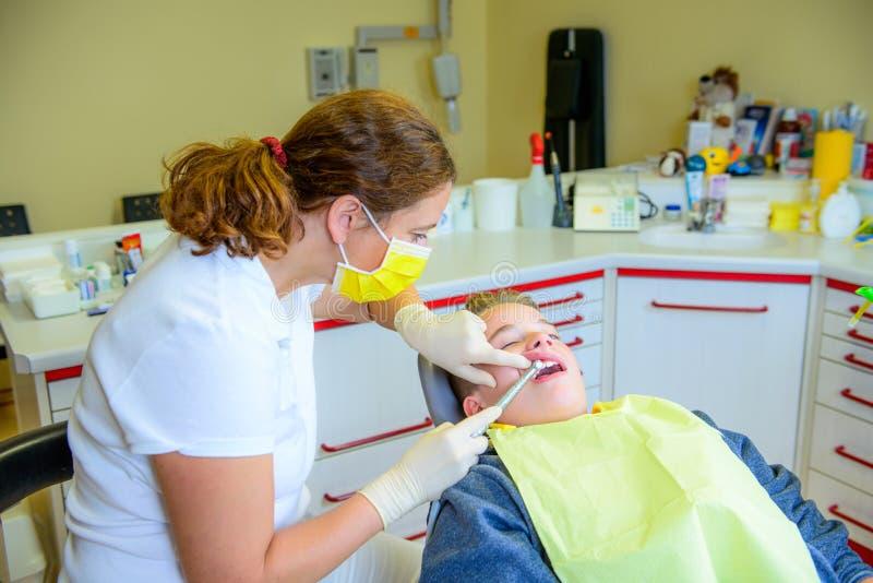 Tiener bij een vrouwelijke tandarts` s chirurgie stock foto