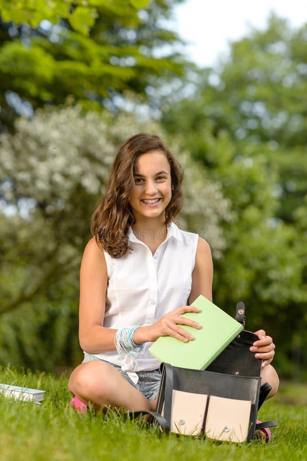 Tiener de zittingsgras van de studentenvrouw met boeken stock afbeeldingen