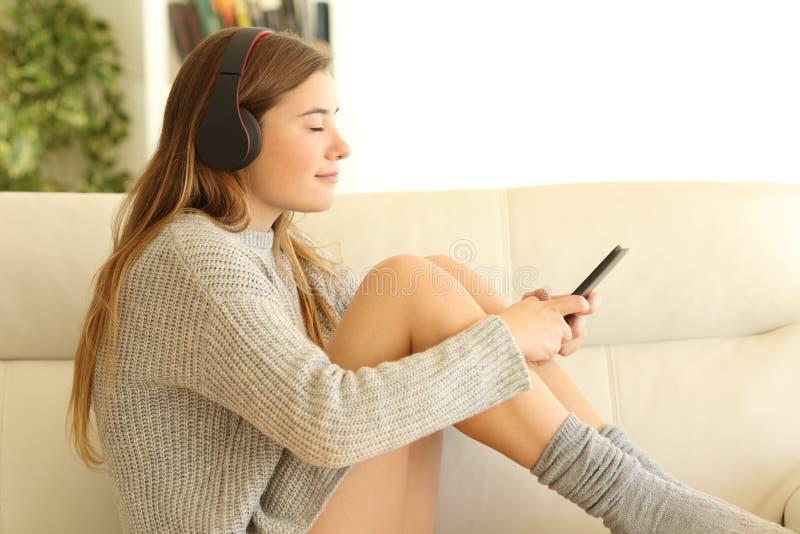 Tiener die aan muziek luisteren die hoofdtelefoons op een bank dragen royalty-vrije stock afbeelding