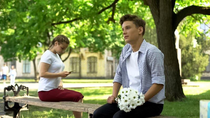 Tiener die aarzelen bloemen aan meisje in park voor te stellen, dame die smartphone gebruiken stock fotografie