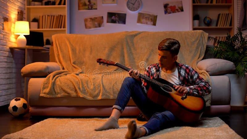 Tiener die bestudeert gitaar te spelen die over de hobby van de musicuscarri?re, levensstijl droomt royalty-vrije stock afbeelding
