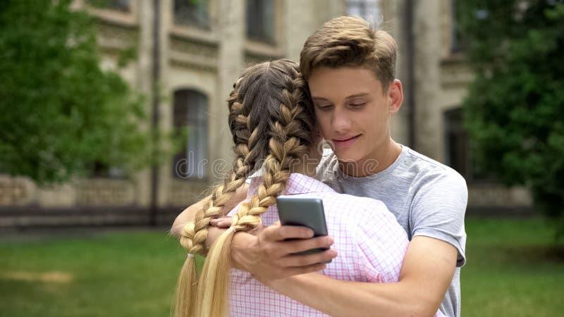 Tiener die celtelefoon met behulp van terwijl het koesteren van meisje, dat door sociale netwerken wordt geabsorbeerd stock foto's