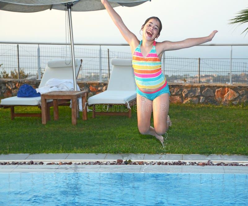 Tiener die in de pool springen stock afbeelding