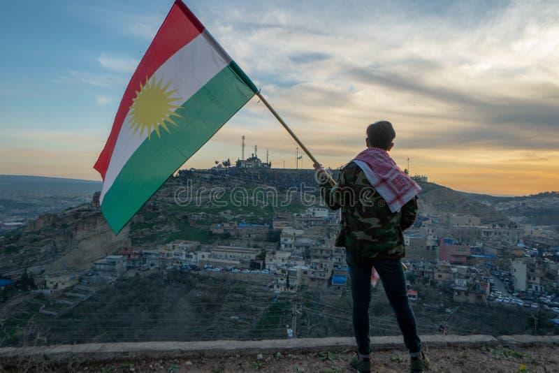 Tiener die de vlag van Koerdistan in noordelijk Irak houden in zonsondergangtijd royalty-vrije stock fotografie