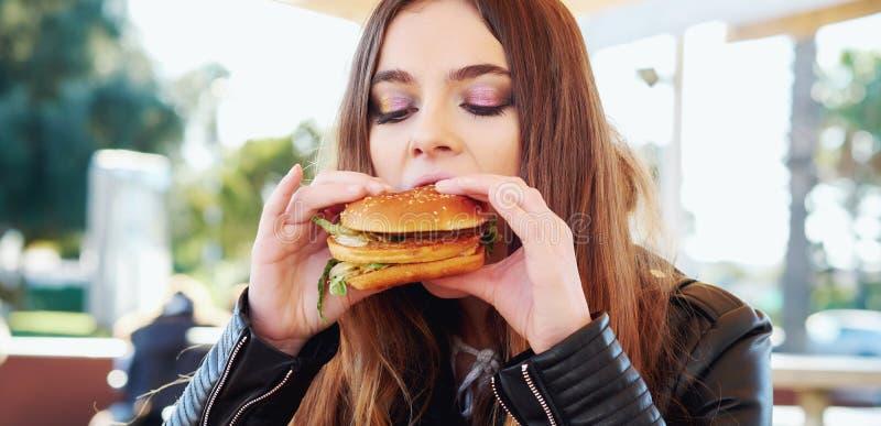 Tiener die een hamburger eten royalty-vrije stock afbeeldingen