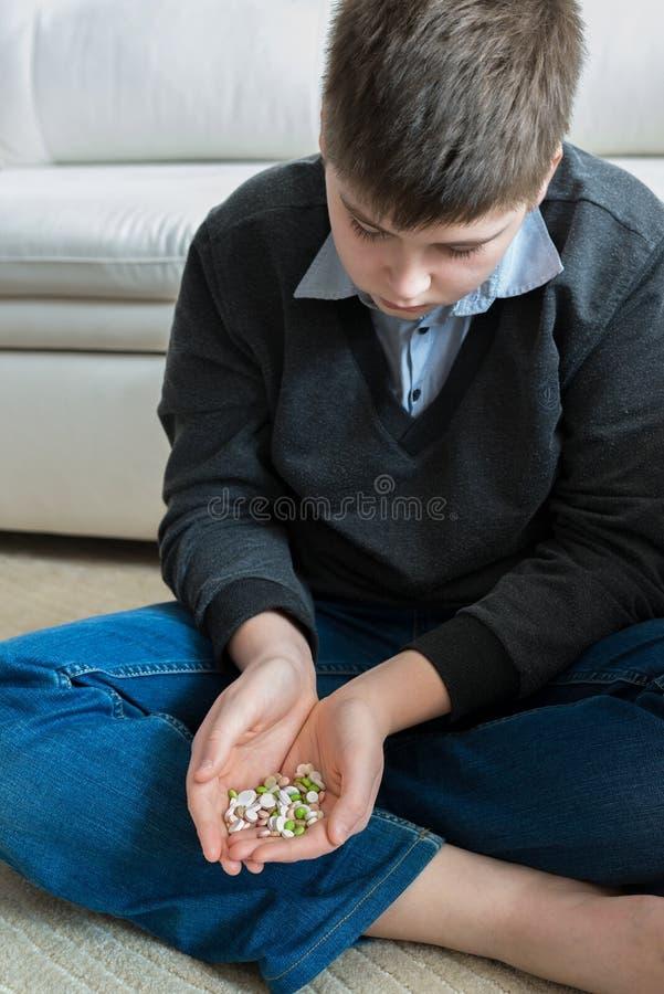 Tiener die een handvol pillen houden en over zelfmoord denken stock afbeelding