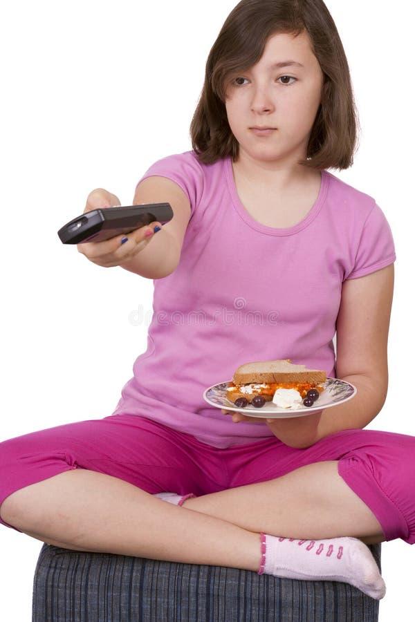 Tiener die een plaat met voedsel en TV-afstandsbediening houden stock foto's