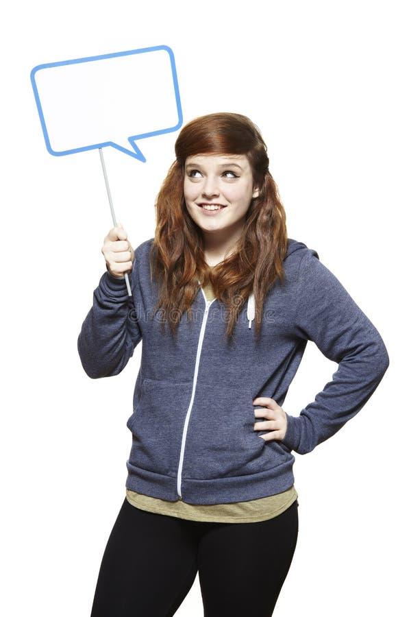 Tiener die het teken van de toespraakbel het glimlachen houden stock foto's