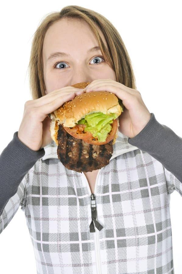 Tiener die grote hamburger eet stock foto