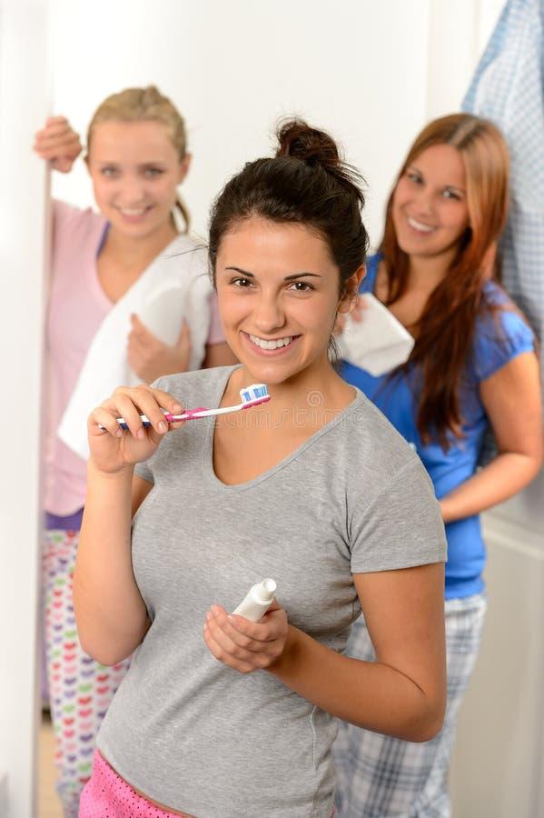 Tiener die haar tanden met vrienden wassen stock afbeeldingen