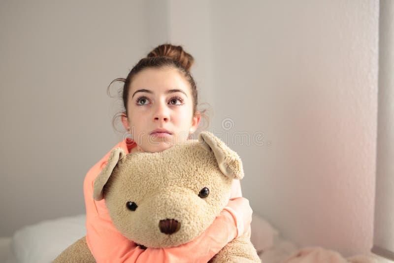 Tiener die haar teddybeer koesteren stock afbeeldingen
