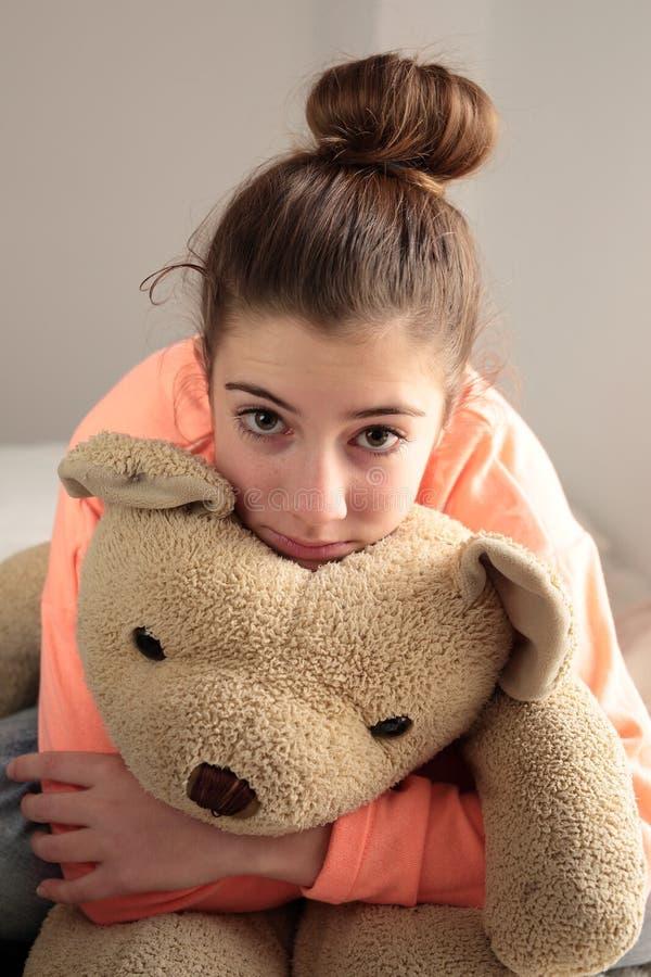 Tiener die haar teddybeer koesteren stock foto