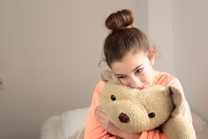 Tiener die haar teddybeer koesteren stock fotografie