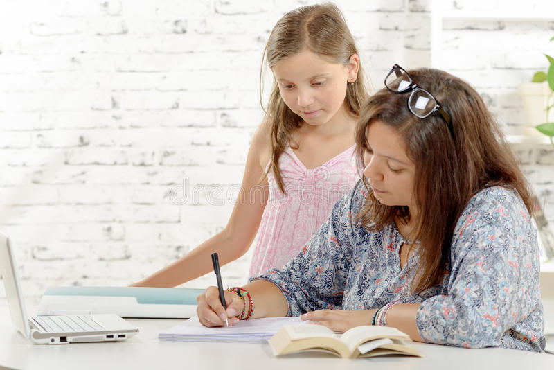 Tiener die haar thuiswerk met haar doen weinig zuster stock afbeelding