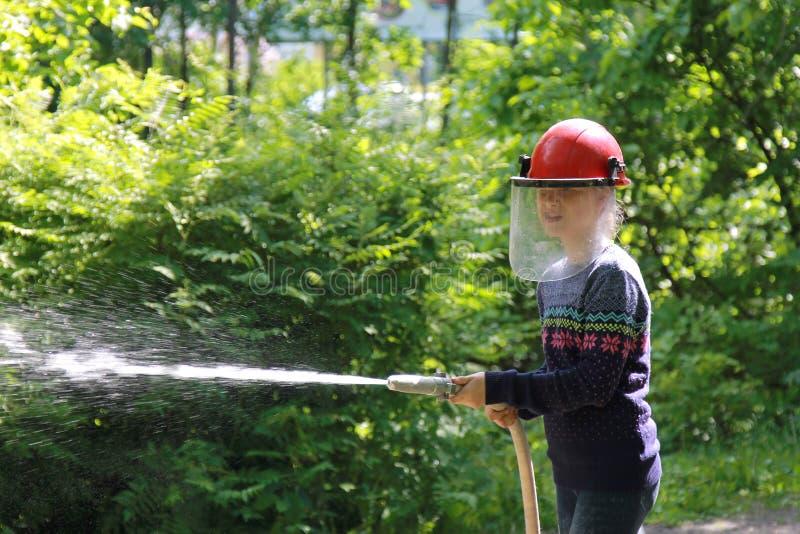 Tiener die het brandbestrijdersberoep leren Het meisje in brandhelm giet water van de slang royalty-vrije stock foto
