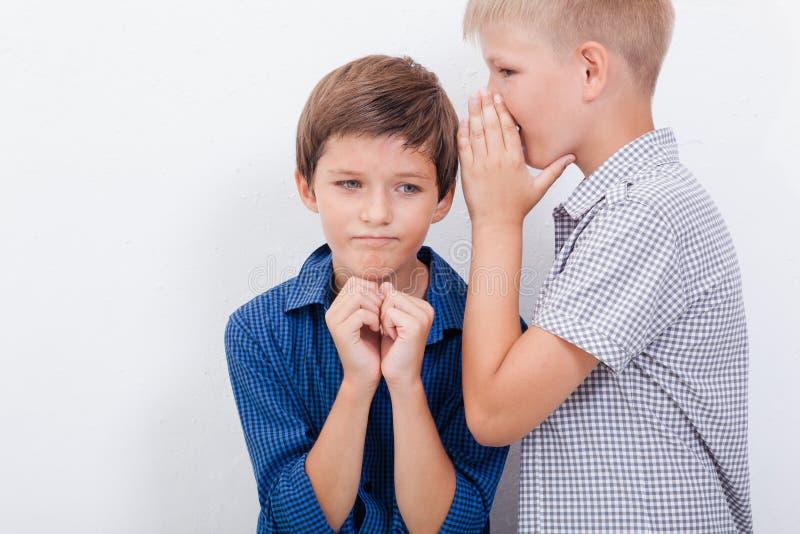 Tiener die in het oor een geheim fluisteren aan stock foto's