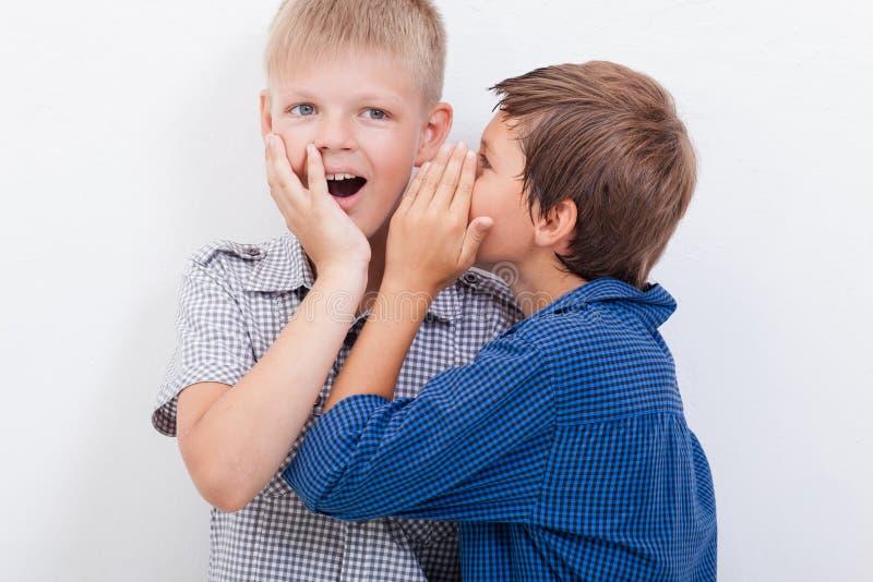 Tiener die in het oor een geheim fluisteren aan stock foto