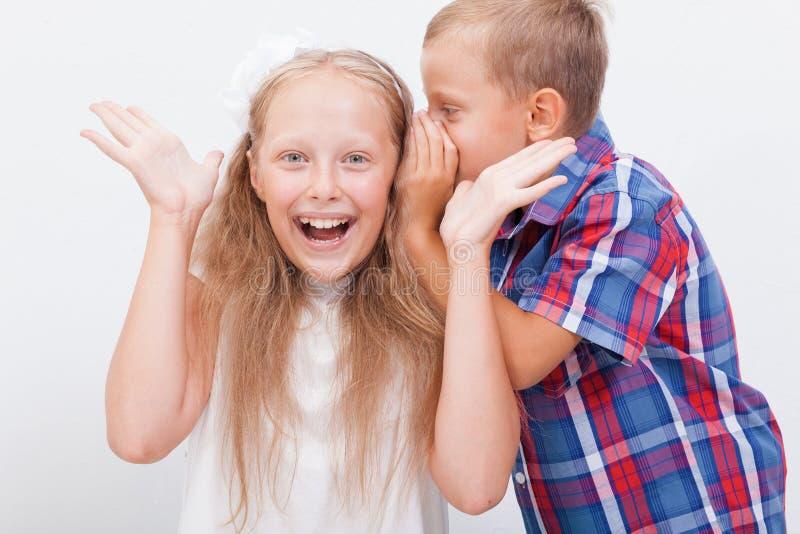 Tiener die in het oor een geheim fluisteren aan tiener stock afbeeldingen