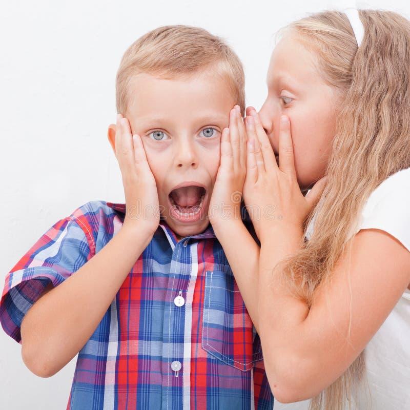 Tiener die in het oor van een geheim fluisteren stock afbeeldingen
