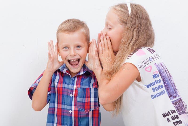 Tiener die in het oor van een geheim fluisteren stock foto's