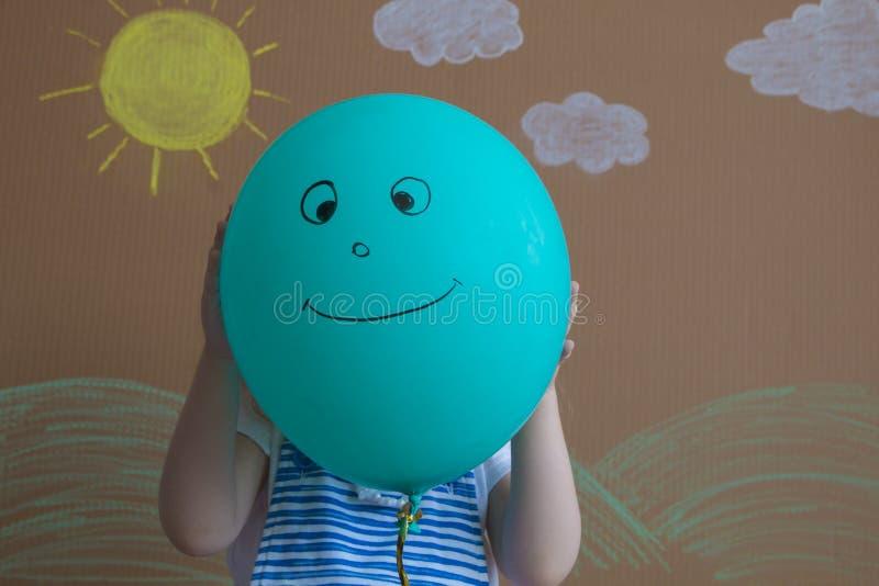 Tiener die hun gezichten achter het glimlachen van ballons verbergen achtergrond van geschilderde zon en witte wolken royalty-vrije stock foto's