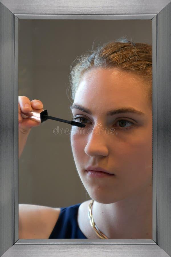 Tiener die mascara toepassen stock afbeeldingen