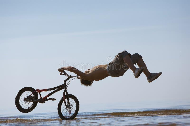 Tiener die met de fiets in water springt stock fotografie