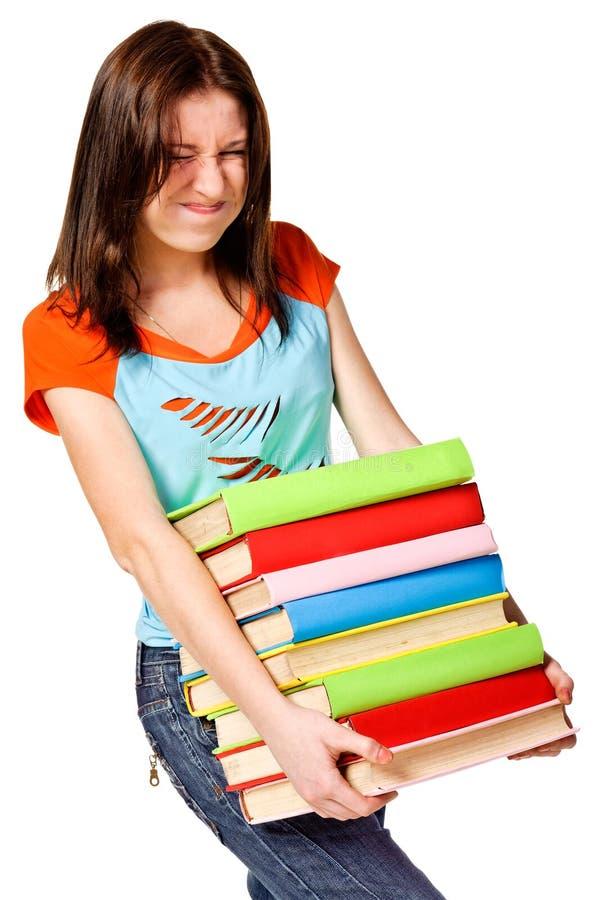 Tiener die met stapel boeken worstelt stock afbeelding