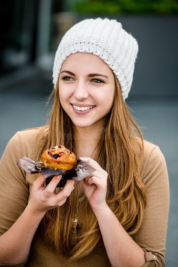 Tiener die muffin eten stock foto's