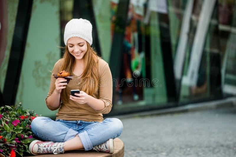 Tiener die muffin eten die in telefoon kijken stock foto's