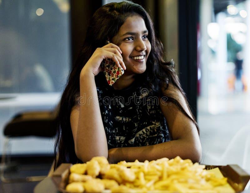 Tiener die op een telefoon spreken die frieten eten stock fotografie