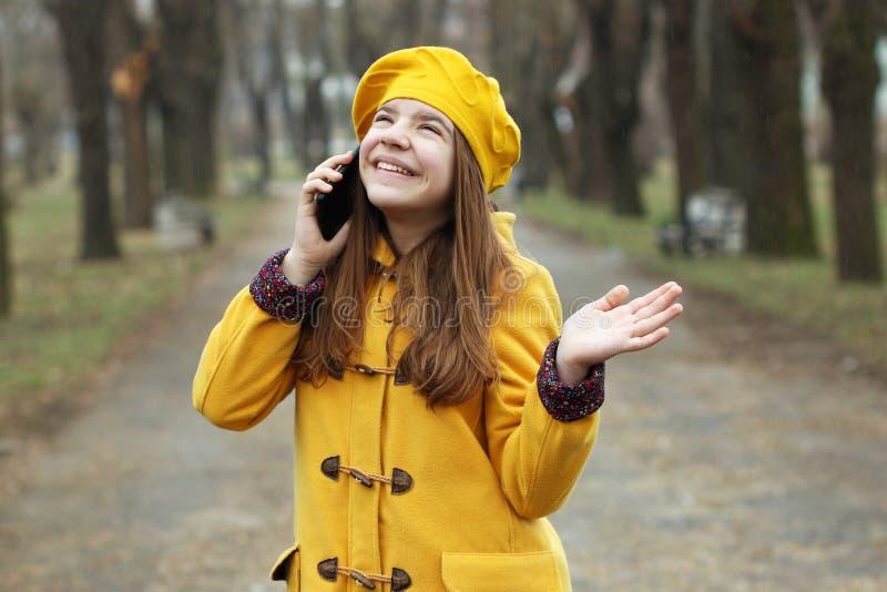 Tiener die op haar celtelefoon spreken terwijl het regent royalty-vrije stock foto