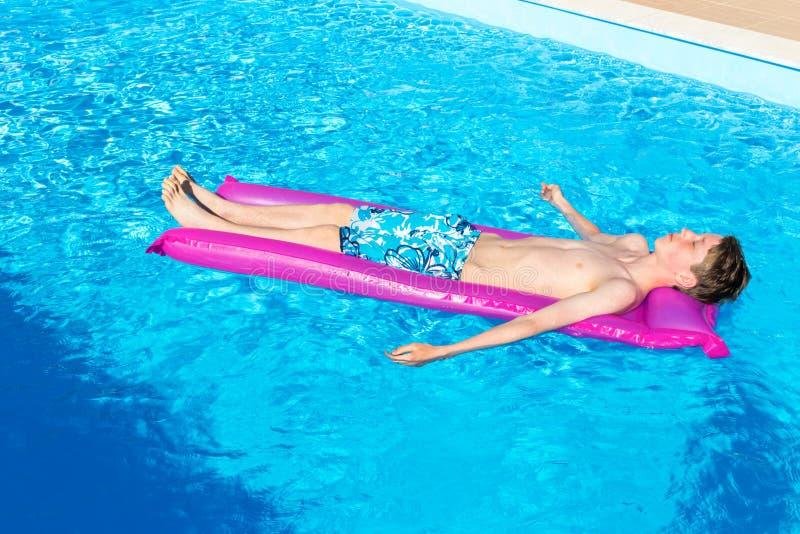 Tiener die op luchtmatras in zwembad liggen royalty-vrije stock foto