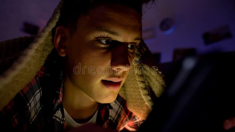 Tiener die of op smartphone babbelen spelen die onder deken, gadgetverslaving liggen stock afbeelding