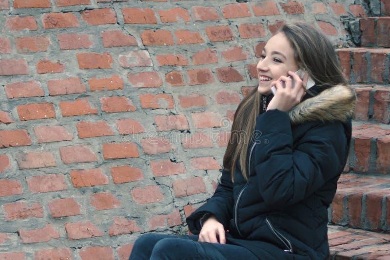 Tiener die op smartphone buiten spreken stock afbeelding