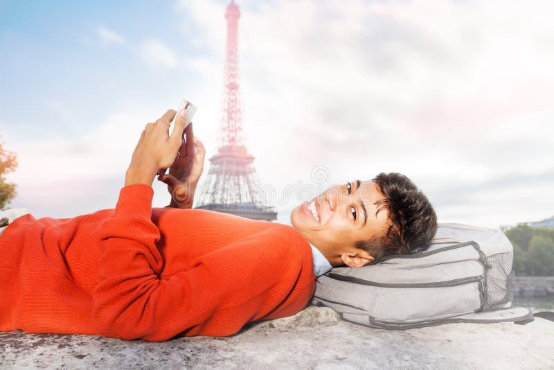 Tiener die op stadsstraat leggen en telefoon met behulp van royalty-vrije stock afbeelding