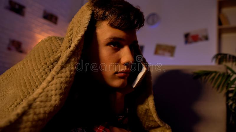 Tiener die op telefoon tot laat spreken - nacht, die onder deken, mededeling liggen stock afbeeldingen